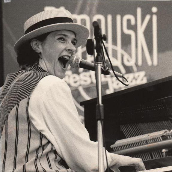 Mimi Blais playing a piano and wearing a hat